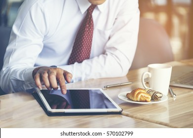 Businessman feeling happy and relax while sitting in Coffee shop and playing social media to search stock Marketing on his tablet after finished a meeting in the office - Business Marketing concept