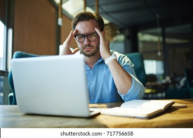 Businessman feeling headache while doing distance work in coffee shop tired with failure of plans, male entrepreneur overworked solving problems with startup project exhausted with hard schedule