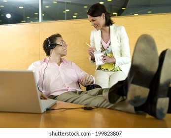 Businessman and female colleague in office having lunch break