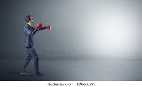 Businessman fighting with boxing gloves in an empty space