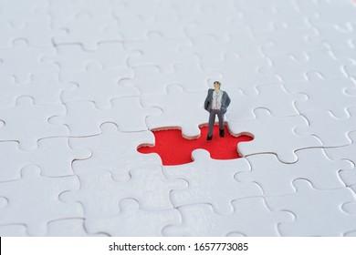 Businessman figurine on jigsaw piece.