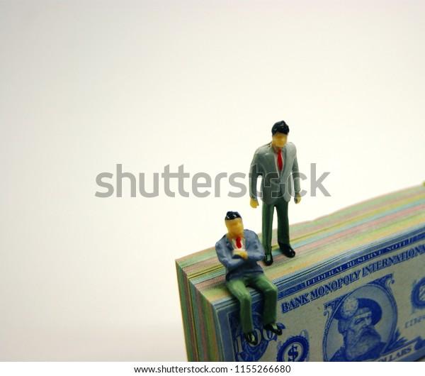 Businessman Figurines On Bonded Monopoly Money Stock Photo