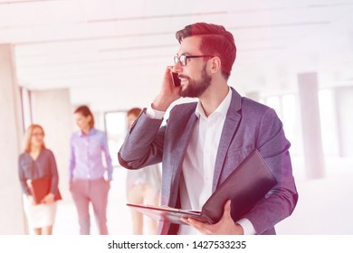 Businessman with file talking on mobile phone against colleagues in new office