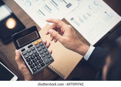 Businessman or financial adviser using calculator calculating and analyzing data at working desk