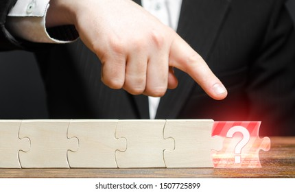 Businessman finger points to the absence of a component in the puzzle chain. Missing or missing component or element. Not enough to complete the project. Management of risks