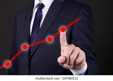 businessman finger touching red rising arrow over dark background