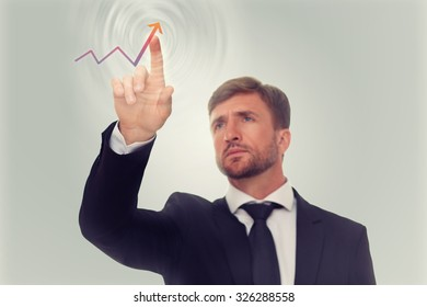 Businessman finger touching red rising arrow over light background. Handsome man demonstrating income and prosperity of the company.