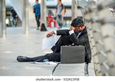 businessman fired from job sitting sad outside office in city background ,  many depression surge this asia man after no work