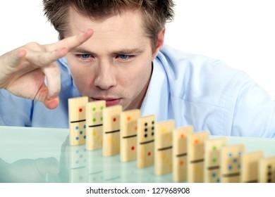 Businessman flicking dominoes