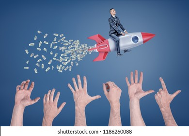 A businessman flies sitting on a rocket that leaves a tail of money with many giant hands trying to catch it. Success and wealth. Wealth attracts vultures. Envy and greed.