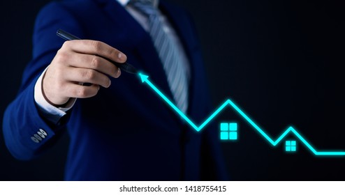 a businessman flocking on a black background draws a growing graph of real estate on a touch screen; business concept;