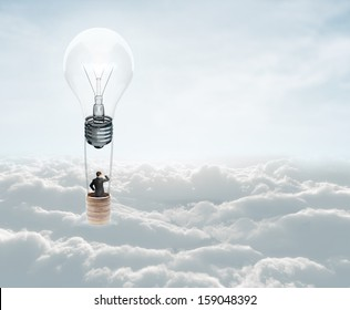businessman flying in air baloon with lamp