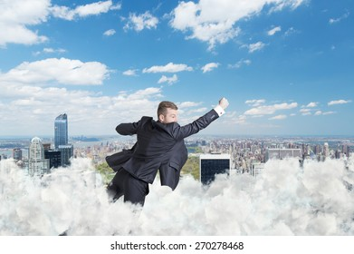 Businessman is flying over the central park in New York through the cloud