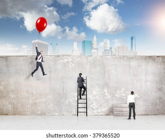 A businessman flying a red balloon, a businessman climbing a ladder and one standing at a concrete wall separating them from New York, blue sky above. Concept of reaching aim.