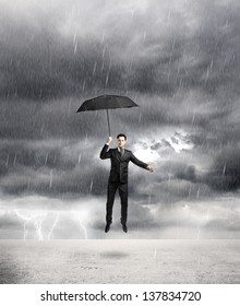 businessman flying with umbrella in storm