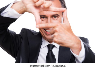 Businessman focusing at you. Playful mature man in formalwear gesturing finger frame and looking through it while standing isolated on white background