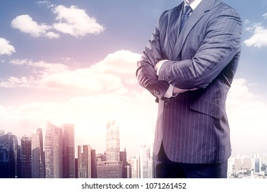 Businessman with folded arms standing on abstract city background. Success and work concept