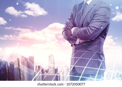 Businessman with folded arms standing on abstract city background. Global business concept. Double exposure