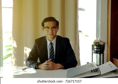 Businessman with folder of paperwork sitting in at the table in the office