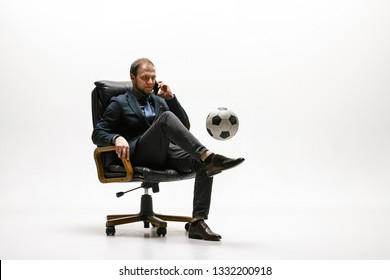 Businessman with football ball in office. Soccer freestyle. Concept of balance and agility in business. Manager perfoming tricks while sitting on chair and speaking on the smartphone isolated on white