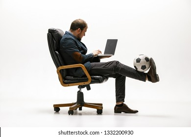 Businessman with football ball in office. Soccer freestyle. Concept of balance and agility in business. Manager perfoming tricks sitting on chair and working on laptop isolated on white studio