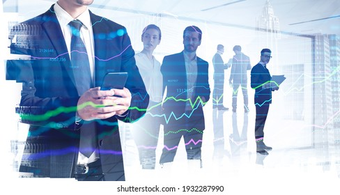 Businessman in formal suit checking stock market rates in smartphone. Hologram charts. Business and financial success concept. Double exposure. businesspeople on background