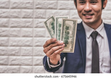 Businessman in Formal Suit Having Dollar Money in Hand , Finance , Investment , Business Concept