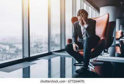 Businessman in formal suit is sitting on orange armchair and holding his head in depression after phone call about his company went bankrupt with copy space for text, your logo or advertising message