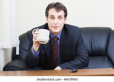 Businessman in formal wear with cup sitting on black sofa