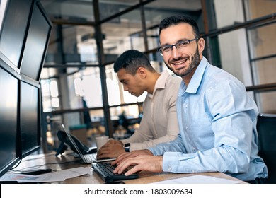 Businessman in formalwear sitting near partner, working in office with modern monitor and checking global currency index on fund exchange