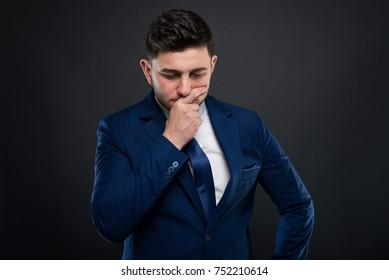 Businessman in formalwear sitting in pensive mood with hand to his chin