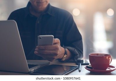 Businessman, freelancer using mobile smartphone, working on laptop computer. Man browsing internet on smart phone with cup of coffee on table, online working from coffee shop, cloud storage technology