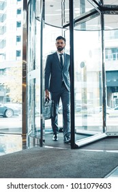 Businessman in a fromal suit in a business center enter the building with briefcase