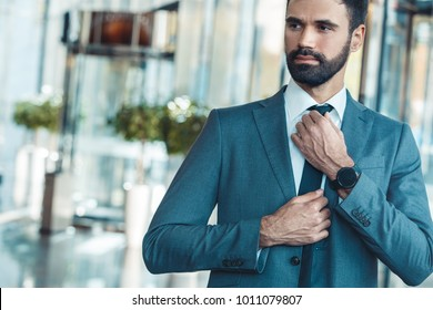 Businessman in a fromal suit in a business center tighten a tie