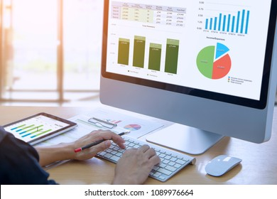 Businessman in front of modern computer with colorful pie and bar graphs analysing business performance accounting data