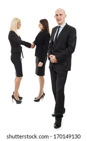Businessman in front and two business women shaking hands in the background out of focus