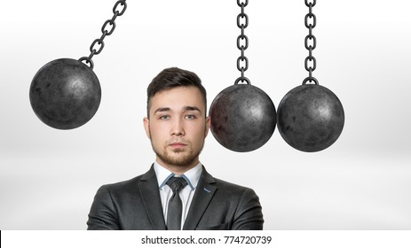 A businessman in a front view stands with his head dangerously put between several wrecking balls and one ready to hit. Dangerous position. Put in jeopardy. Problems ahead.