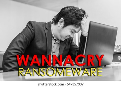 businessman frustrated, confused and headache by WannaCry ransomware attack on desktop screen on labtop in office, cyber attack internet security concept