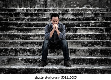 Businessman in frustrated depression sitting on the stairs, in scary abandoned building. The concept of Major depressive disorder, unemployed, sadness, depressed and human problems in dark tone.