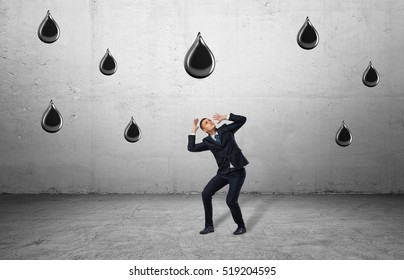 Businessman in full growth protects himself against huge falling oil drops. Acid rain. Environmental pollution. Oil refining. Industry implications. Oil industry.