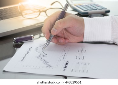 Businessman or fund manager review Mutual Fund information with performance line graph and benchmark with pen calculator and computer laptop.