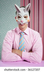 Businessman with funny rabbit easter mask portrait over wallpaper