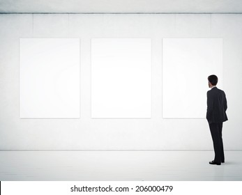 Businessman in gallery room looking at empty frames