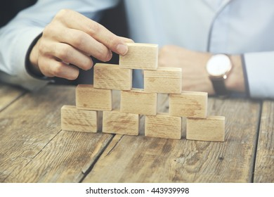 Businessman gambling placing wooden block on a tower