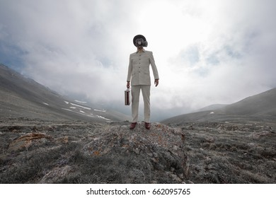Businessman in a gas mask in the mountains