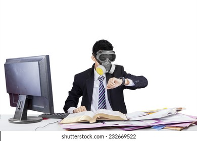 Businessman with gas mask working in workplace and looking at his timepiece