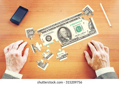 Businessman gathers One hundred American dollars as a set of puzzles on the wooden desk