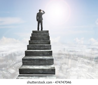 Businessman gazing on top of concrete stairs, with sky sun clouds background.