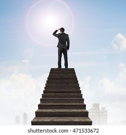 Businessman gazing on top of wooden stairs, with sky sun clouds background.