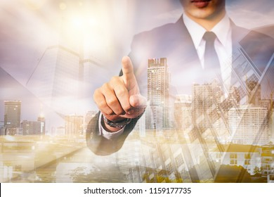 Businessman with gesture The double exposure image of the business man standing back during sunrise overlay with cityscape image. The concept of modern life, business, city life and internet of things